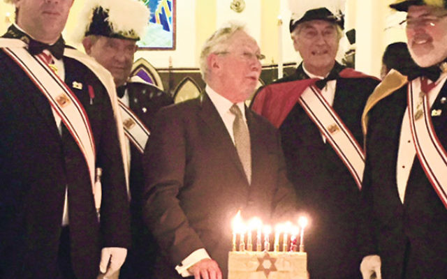 Rabbi Norman Patz lights the menora surrounded by members of the Knights of Columbus.