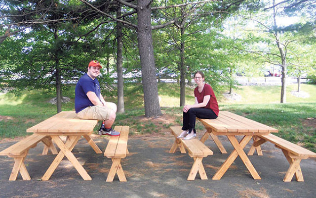 Kenny Pepper and Lara Wellerstein relax on the picnic tables he built.