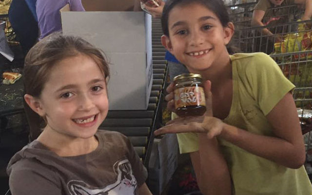 Liat Pineles holds up a jar while packing food for the needy.