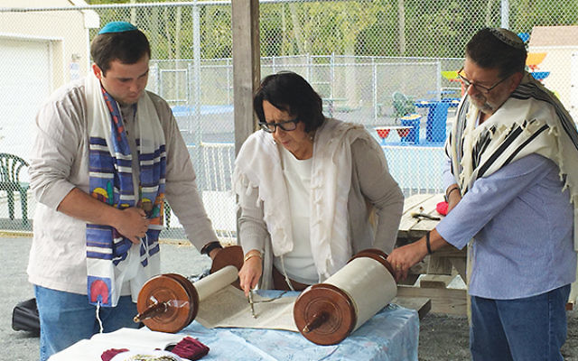 Rabbi Ellie Shemtov of Congregation Kol Am reads Torah with two attendees at the synagogue's annual second day of Rosh HaShanah service in a Freehold park. The service is free and open to the public. Photo courtesy of Congregation Kol Am