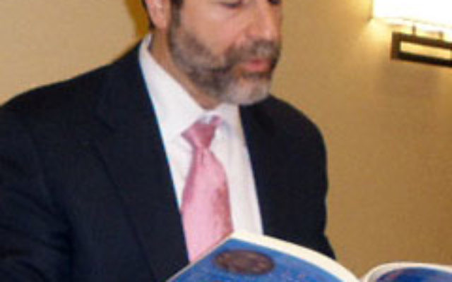 Rabbi Kerry Olitzky, executive director of the Jewish Outreach Institute, reads from one of his books during a Nov. 30 talk at the Highland Park Conservative Temple.