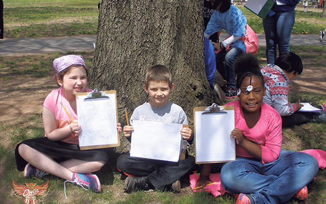 Three second-graders — from left, RPRY student Sarah Menashe and Bartle School students Keith McGarty and Zaniya Smith — sit on the bank of the Raritan River in Donaldson Park displaying the pictures they drew of the water and its surroundings