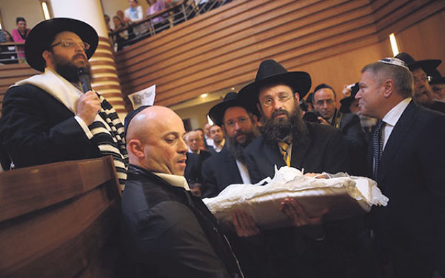 An infant being carried before his circumcision at an Orthodox synagogue in Berlin in 2013.