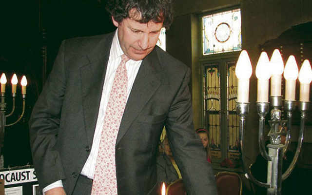 Simon Rosenbach, soon to be ordained as rabbi at Congregation Ahavas Sholom in Newark, lit a candle at his synagogue's Holocaust memorial in May 2011.