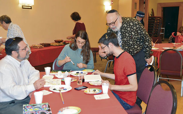 """Artist Mordechai Rosenstein gives Igor Muraviev some tips during the family program at Highland Park Conservative Temple-Congregation Anshe Emeth. Creating their own works of art are Nadine Goldman and Ari Klein.<span style=""""line-height: 1"""