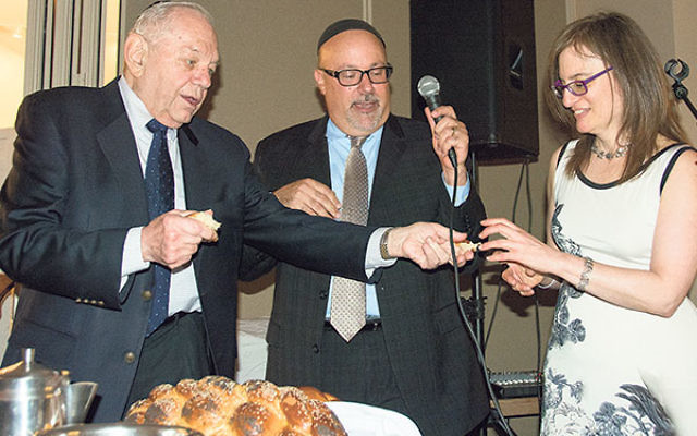 Rabbi William Horn, left, recites the HaMotzi while the honorees look on.