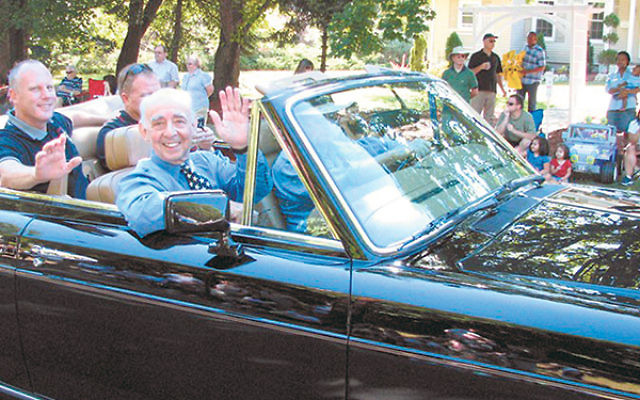 Waving to the crowd from the front seat of a Rolls Royce, Jack Schrier greets constituents during the 2008 Labor Day parade in his hometown of Mendham.