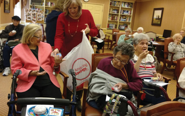 Jennine Shpigel hands Anna Freno a Hanukka gift bag from the JCC.
