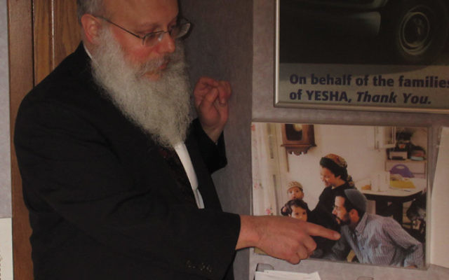 Rabbi Asher Herson points to a photograph of Yosef Twito on the wall of the Chabad Center of Northwest New Jersey in Rockaway.