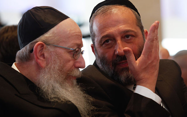 Shas party leader Aryeh Deri, right, speaking with United Torah Judaism leader Yaakov Litzman at the opening session of the 20th Knesset, March 31, 2015. (Nati Shohat/Flash90)