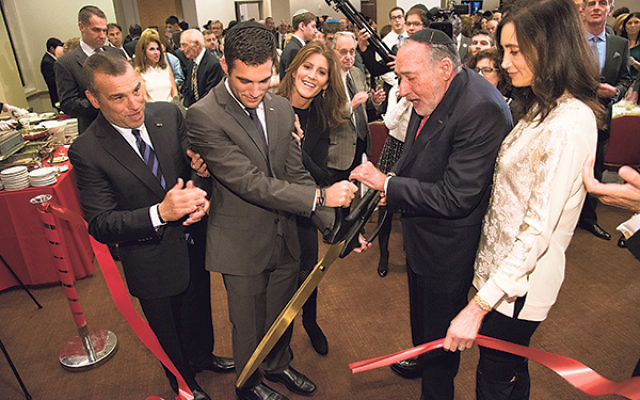 Joining honoree Mike Shevell, fourth from left, in a ribbon-cutting ceremony dedicating the Shevell Family Synagogue at Rutgers Chabad are, from left, son-in-law Robert Cohen, grandson Zachary Cohen, and daughters Susan Shevell Cohen and Nancy Shevell McC