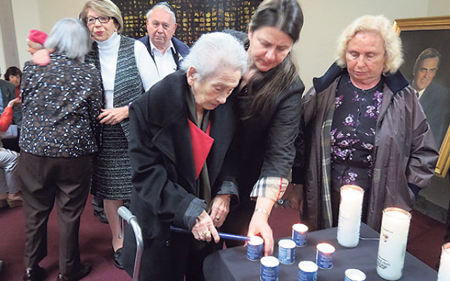 Shoa survivors and members of the next generations light candles for loved ones murdered by the Nazis.