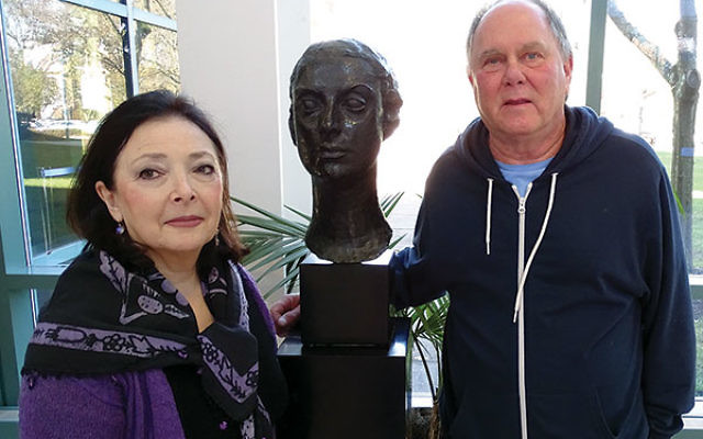 Donor Israel Yanoff and Holocaust Council director Barbara Wind admire the bust of a young unknown Holocaust victim. The sculpture and 39 other Shoa-related works of art are on display at the Aidekman campus in Whippany until Nov. 18.