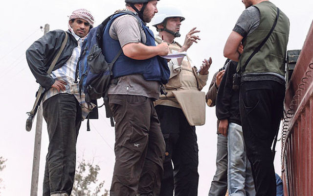 In this handout image made available by the photographer, American journalist Steven Sotloff, center with black helmet, talks to Libyan rebels on the Al Dafniya front line, 15 miles west of Misrata, June 2, 2011. Sotloff was kidnapped in August 2013 near