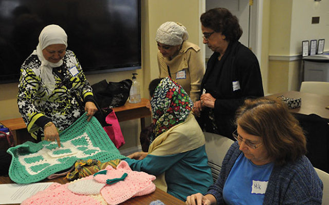 The stitchers learn how to make a baby quilt by crocheting granny squares.