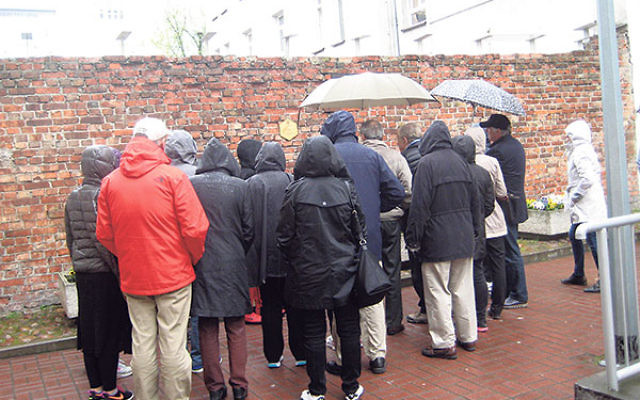 Members of Temple B'nai Abraham gather outside a wall of the Warsaw Ghetto.