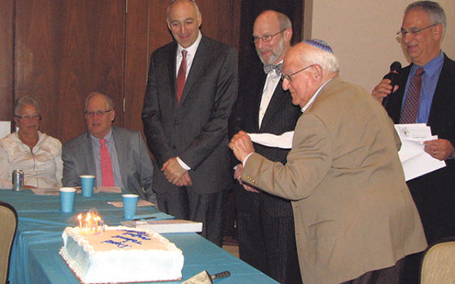 David Schechner, about to put out the candles in his own fashion — without blowing (to avoid spit), but rather by whipping a cloth napkin at the flames. With him are, from left, seated, Sharon and Jimmy Schwarz and, standing, Rabbi Mark Cooper, Rabb