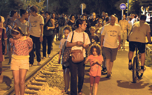 Tamar Cohen and her daughters Nina, left, and Magali, in August at one of the weekly anti-racism marches of the Hand in Hand community, on the Train Tracks Park that connects Jewish and Arab neighborhoods in southern Jerusalem. The T-shirts worn by some o