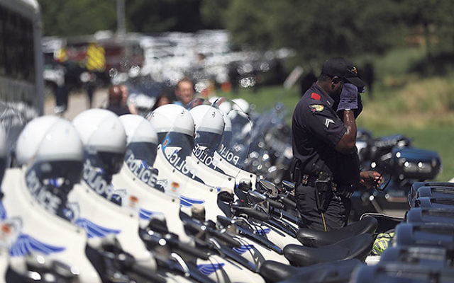 A Dallas police officer wiping his face at the funeral for his slain colleague Michael Smith at The Watermark Church in Dallas, July 14.