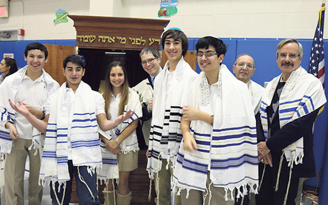 Members of Congregation Torat El joined students at the Solomon Schechter Day School of Greater Monmouth County celebrating the donation of a new Torah scroll; at the Jan. 29 event are, from left, eighth-graders Scott Rubin, David Vignapiano, and Samara B