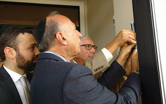 Jeffries Shein, right, and Roy Tanzman affix the mezuzah on the doorpost of Torah Links of Middlesex County's new Marion and Norman Tanzman Center for Jewish Life. Rabbi Shlomo Landau looks on. Photo by Debra Rubin