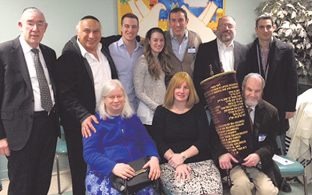 """The descendants of Chaya """"Ida"""" and Gershon Goldberg were reunited with a lost family Torah scroll, including, from left, front row, grandchildren and siblings Sharon Cohen, Judy Goldrich, and Gershon Goldberg, and, rear, family friend Rabbi Be"""
