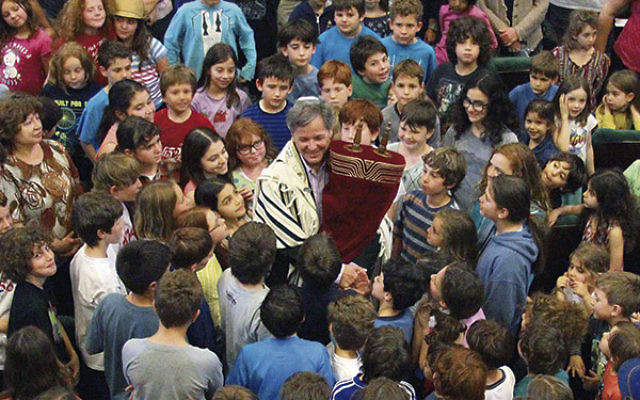 "Rabbi John Rosove celebrates with the ""Torateinu ARZA"" scroll among students at Temple Israel of Holywood Day School in Los Angeles. The scroll will be at three NJ Reform synagogues May 30-June 4 before being donated to a Reform congregation i"