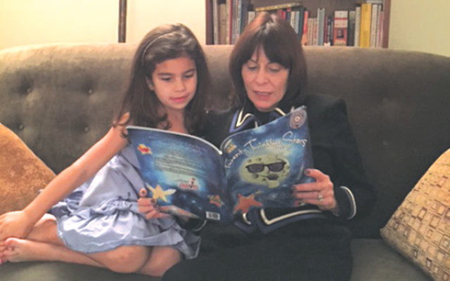 Laurie Schloff reads from her new book, Twenty Twinkling Stars, with kindergartener Emily Moss.
