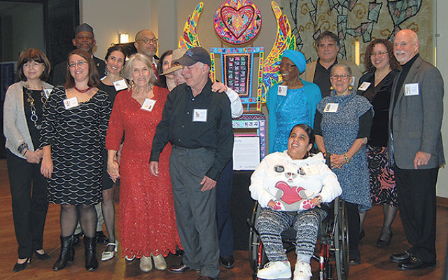 """At the Wae Center's 10th anniversary dinner, founder and director Marilynn Schneider, third from left, with the lead artists and some of their Wae cocreators of the """"Chairs of Inclusion."""""""
