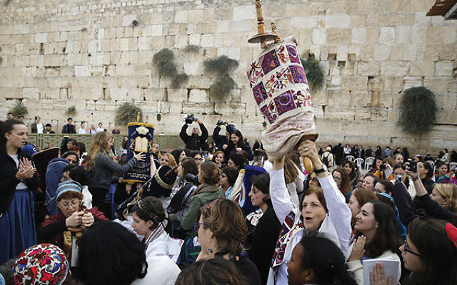 Anat Hoffman, founder of Women of the Wall, raises a Torah scroll during a 2016 protest demanding equal prayer rights at the Western Wall. MENAHEM KAHANA/AFP/Getty Images