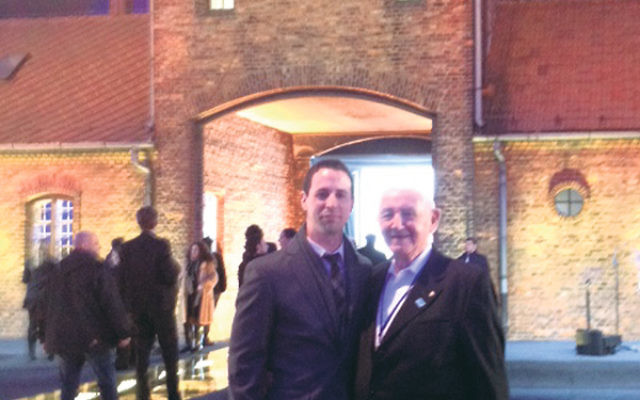 Avi and Cantor David Wisnia in front of the gate to the death camp at Birkenau.