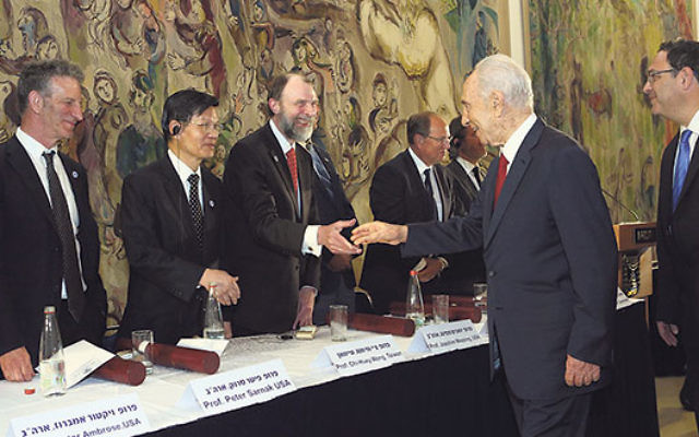 Then Israeli President Shimon Peres congratulates Wolf Prize recipients, including Rutgers microbiologist Dr. Joachim Messing, third from left, and Princeton mathematician Prof. Peter Sarnak, left.
