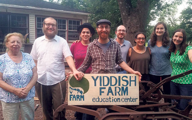 Micah Langer, fifth from left, with other students and staff members at Yiddish Farm. Roza Jaffe, far left, is a Holocaust survivor from Teaneck who told her life story in Yiddish to the farmers.