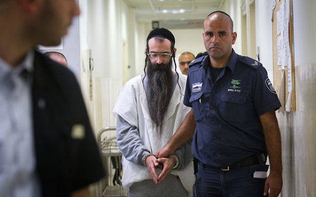 Yishai Schlissel is escorted by police after his hearing at the Jerusalem Magistrates Court on August 11, 2015. (Miriam Alster/Flash90)