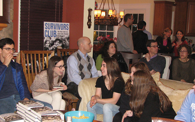 A group of teens and adults gather on April 24 in the North Caldwell home of Lori and Keith Wolf to hear Lori's father, Michael Bornstein, talk about his childhood during and after the war. Photos by Johanna Ginsberg