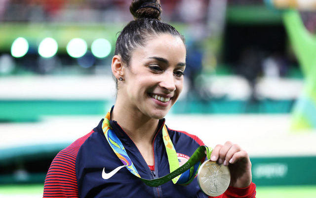 Aly Raisman posing for photographs after winning a silver medal in the all-around competition at the 2016 Rio Olympics at Rio Olympic Arena, Aug. 11, 2016.
