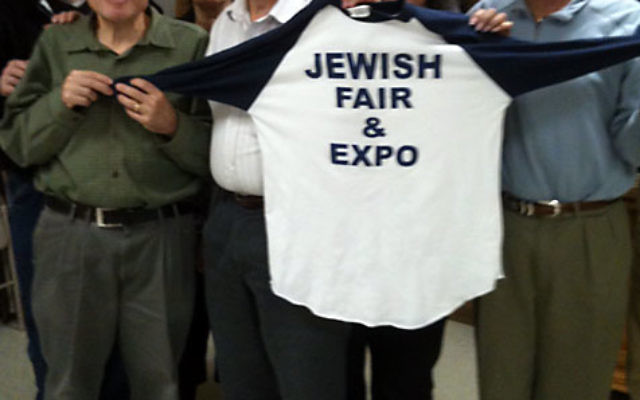Marc Hilton, center, chair of the Jewish Fair and Expo, and his committee show off the event T-shirt.