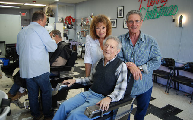 Goldstein takes it easy in his old chair, with current salon owners Carol and Ron Grosso, with whom he worked for 20 years.