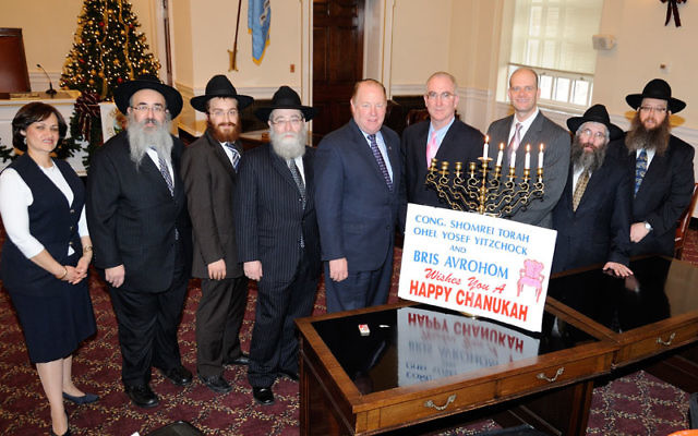 Rabbi Mordechai Kanelsky and his wife Shterney, left, gather at Elizabeth City Hall last year with Mayor Chris Bollwage, center, and other rabbis and officials for the lighting of the menora there. Photos courtesy Bris Avrohom