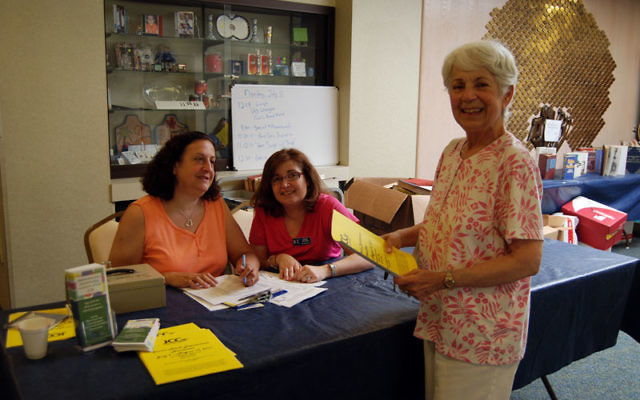 Evelyn Freuler, right, signs in for a JCC adult summer program at Congregation Beth Israel, with volunteers Lori Rosoff, left, and Randy Belfer. Photos by Elaine Durbach