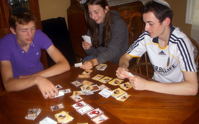 Cholent, The Game! players, from left, Nechemia and Batsheva Kivelevitz, sisters of one of the game's inventors, and a friend, Hirshel Hall, try their hand at the game.