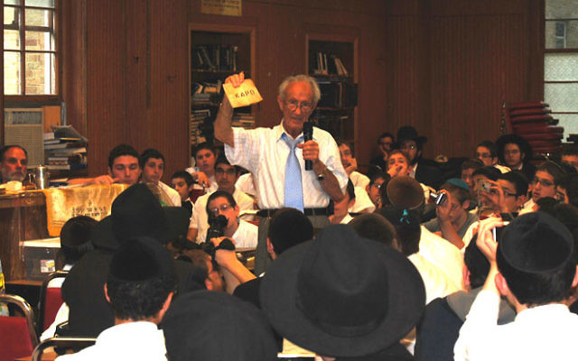 To bring home the reality of the Holocaust to Chabad students in Morristown, survivor Ed Mosberg shows them mementos that he has gathered over the years. Photos by Elaine Durbach