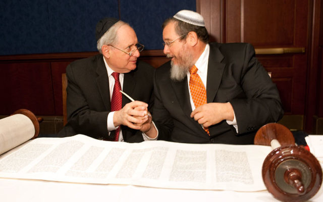 Sen. Carl Levin, left, joins scribe Zerach Greenfield in completing the writing of a Torah scroll for the troops at the U.S. Capitol on May 10. Photo by Stan Barouh