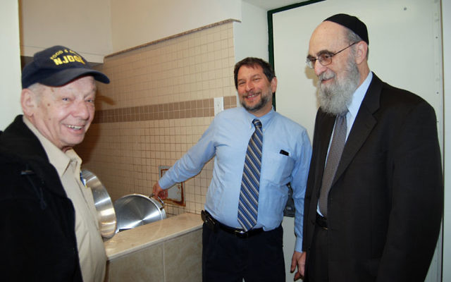 Bill Goldfischer, left, head of the Union Y's food service, and the Y's executive vice president Bryan Fox, center, dipped new utensils in a special mikva at the JEC, accompanied by JEC leader Rabbi Elazar Teitz. Photo by Elaine Durbach