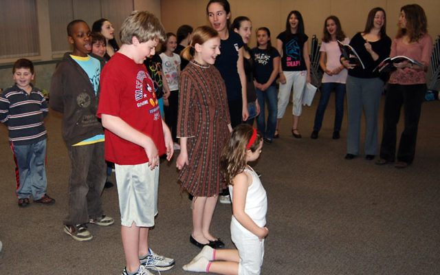 Stars of the JCC's production of Annie, Rachel Weisenthal and Kyle McGee, standing, rehearse with the cast, directed by Beth Kasper, right, and Leslie Glass, second from right.