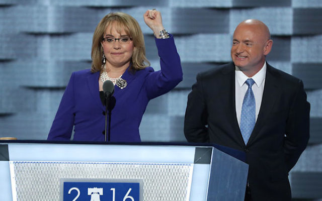 Gabby Giffords waving to the crowd as her husband, retired NASA Astronaut and Navy Captain Mark Kelly, looks on after speaking on the third day of the Democratic National Convention at the Wells Fargo Center in Philadelphia, July 27, 2016. (Alex Wong/Gett