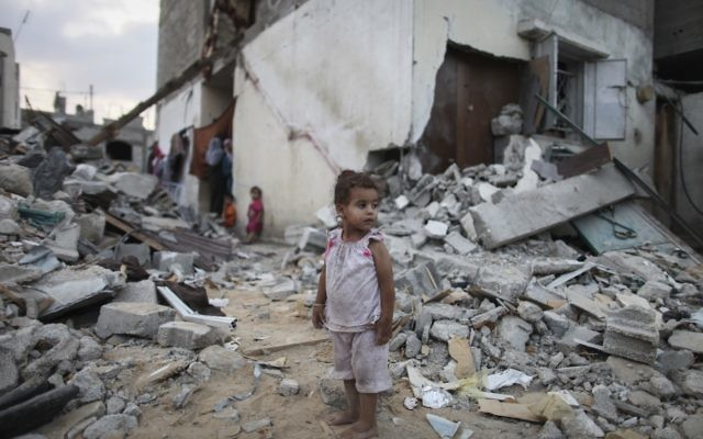 A Palestinian child amid the rubble of homes destroyed by Israeli airstrikes in the northern Gaza Strip, Aug. 18, 2014. (Emad Nasser/Flash90)