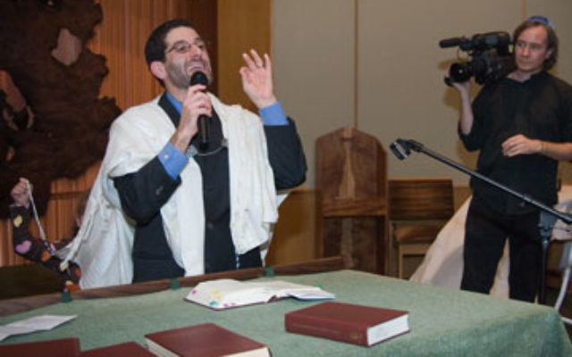 A cameraman for the ABC documentary A Place for All: Faith and Community for Persons with Disabilities films Rabbi Darby Leigh of Bnai Keshet during Simhat Torah services in October.