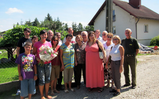 Ruth Rosenfeld, front, fifth from left, and family members join descendants of Julia Wala in front of the home where she hid Rosenfeld as a child.