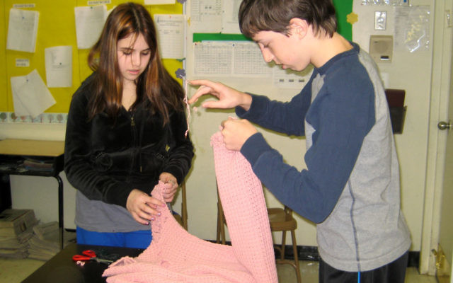 Solomon Schechter Day School of Greater Monmouth County students Ariella Belote and Andrew Goldwasser reuse yarn from a sweater to make friendship bracelets for their counterparts in Israel.